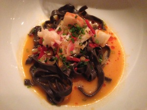 Spicy squid ink tagliatelle with lobster, bell peppers and tomato confit