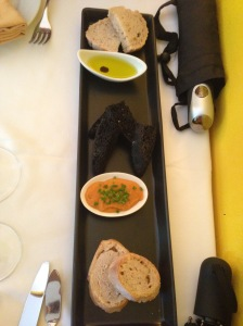 (top to bottom) White bread, olive oil, squid ink bread, carrot sauce, oregano bread