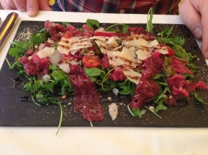 "Veal carpaccio, almond ""farofa"", cheese, arugula and truffled vinagrette"