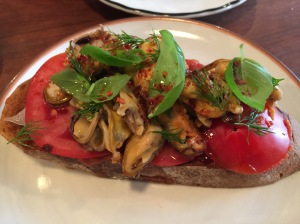 Tomato on bread topped iwth mussells and lardo.