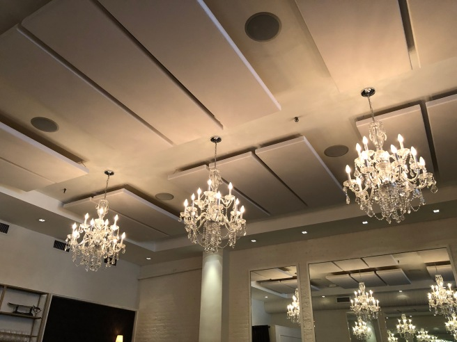 chandeliers reflect in the mirrors