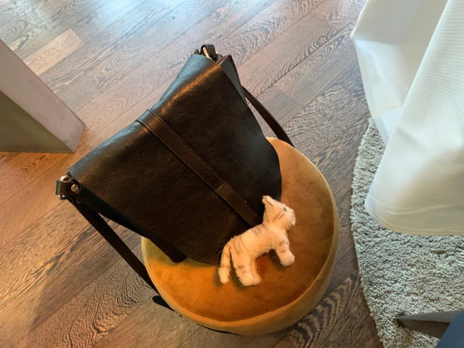 Frankie lounged on the purse stool